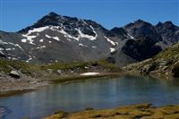 Alpine trekking adventure peak bagging in Alps - lake surrounded by mountains